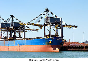 Bulk carrier - Huge cranes unloading ore from a bulk carrier
