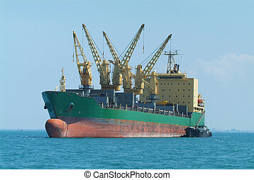 Empty bulk ship at anchor in tropical waters