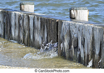 wooden bulkhead with water seeping through the boards