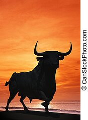 Bull against sunset, Spain. - Bull statue against an orange...
