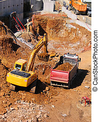Yellow bulldozer and dump truck at a new construction site