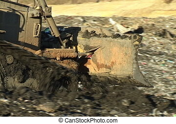 Bulldozer covers the day's garbage with a layer of dirt at a landfill.