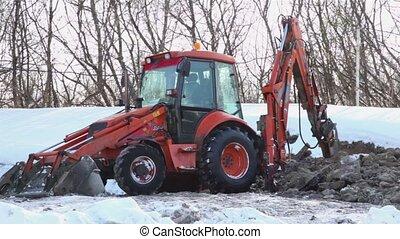 Bulldozer boring terrestrial rocks in winter, pile of ground...