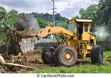 A worn, recycled bulldozer with polluting smoke plume clearing plant debris and soil with lifted scoop, preparing and leveling a tropical terrain in a residential area with mountains in the background.
