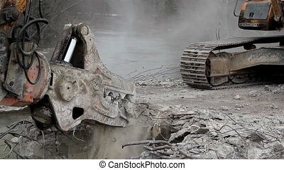 Bulldozer destroying a bridges heavy equipment with pinchers removing damaged bridge