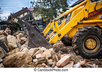 bulldozer loading demolition debris and concrete waste