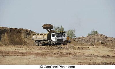Bulldozer loading sand transportation truck on construction site. Construction equipment. Crawler bulldozer moving sand.