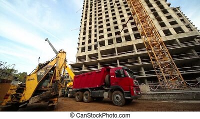 Bulldozer loads truck at building place of living house
