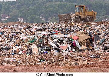 Bulldozer on a landfill site - A bulldozer moving garbage on...