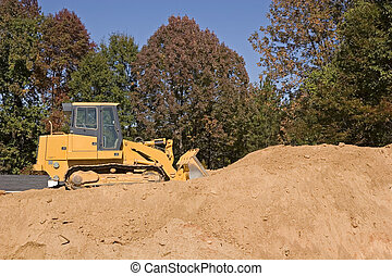 Heavy construction equipment on top of a large pile of dirt