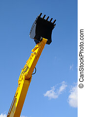 Bulldozer shovel opposite blue sky