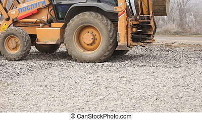 bulldozer spreads gravel on the territory