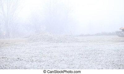 bulldozer spreads gravel on the territory