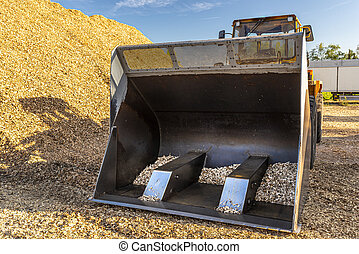 Bulldozer standing in a sawmill between halves of wood chips, against a blue sky.