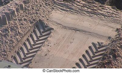bulldozer rakes up ground