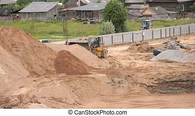 Bulldozer working on large pile of sand in summer - Yellow...