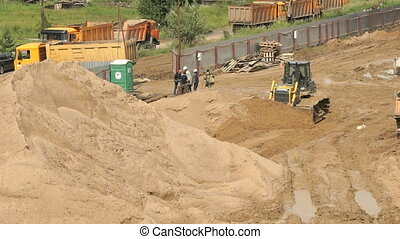 Bulldozer working on large pile of sand in summer - Building...