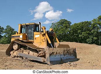 Bulldozer - Yellow bulldozer standing idle on rough earth ...