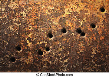 Rusty metallic surfaces perforated with bullet holes.