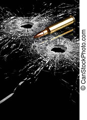 bullet holes in glass with bullet - broken glass isolated on...