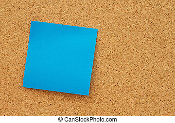 Bulletin board with a blank blue sticky note
