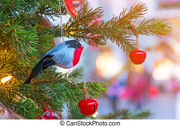 Bullfinch and berries toy decoration on the branches of a Christmas tree.