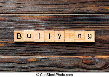 Bullying word written on wood block. Bullying text on wooden table for your desing, concept