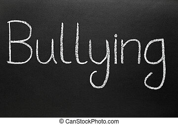 Bullying, written with white chalk on a blackboard.