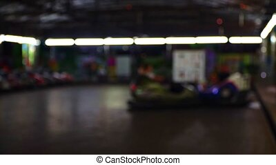 Bumper cars in city amusement park at evening. Blurred video...