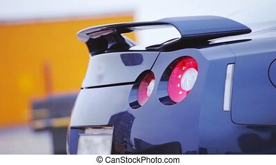 Bumper of bright dark blue new car with red lights. Brand model. Automobile. Cold shades