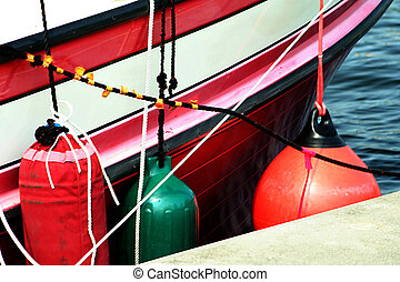 Abstract view of red and white boat with bumpers.