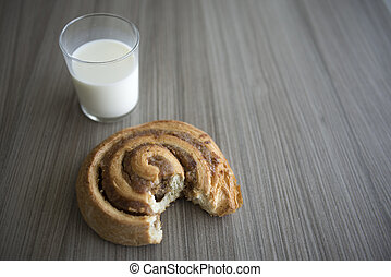 Bun and milk on a wood table