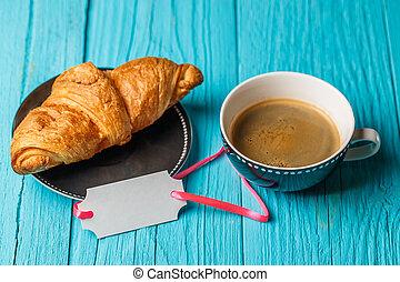 Bun, coffee, card on table