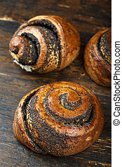 bun with poppy seeds on wooden background