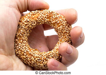 bun with sesame seeds in hand