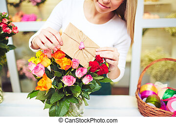 Bunch for holiday - Young florist putting love note in small...