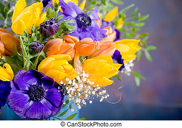 bunch of anemones and tulips on the table