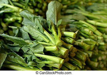 Bunch of Asian fresh mustard greens in Chinatown market. Food background texture.