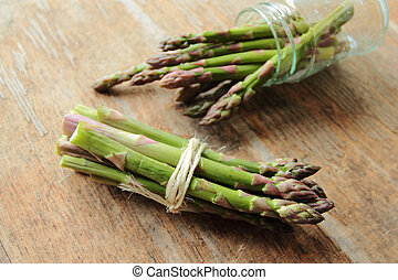 Bunch of asparagus fresh roots on wooden table