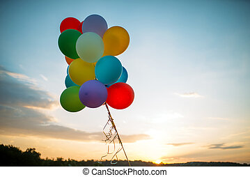 Bunch of balloons flying in the sky at sunset