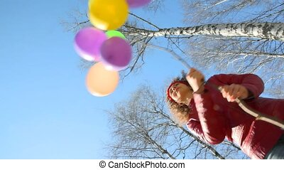 bunch of balloons waving by woman in park - bunch of...