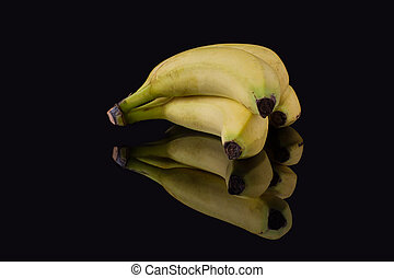 Bunch of bananas in black studio isolated. Four yellow Musa acuminata. Food concept.