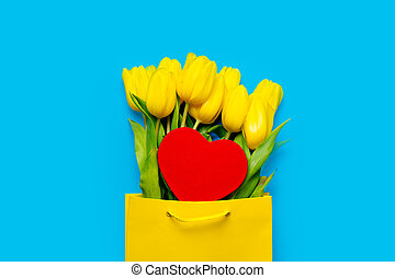 bunch of beautiful yellow tulips in cool shopping bag and heart shaped toy on the wonderful blue background