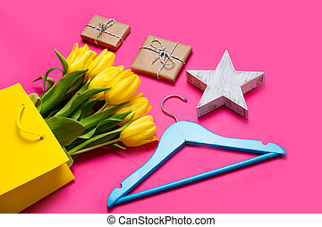 bunch of beautiful yellow tulips in cool yellow shopping bag, hanger, star shaped toy and small gifts on the wonderful pink background