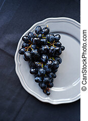 Bunch of black grapes on a plate