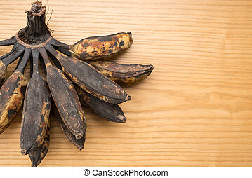 bunch of black overripe bananas on a wooden background with copy space