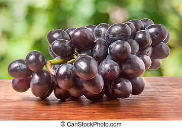 bunch of blue grapes on a wooden table with  blurred background