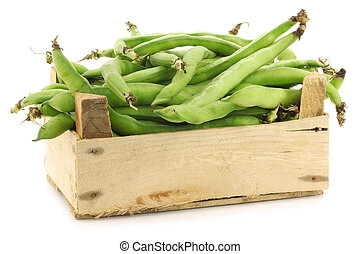 bunch of broad beans in a wooden box on a white background