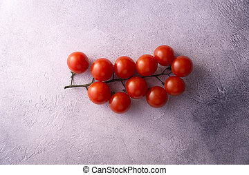 Bunch of cherry tomatoes on white stone concrete table, top view with copy space. Ingredients for cooking.