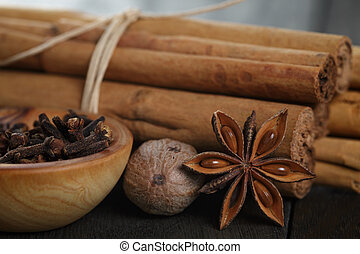 bunch of cinnamon sticks with nutmeg, anise and cloves, on rustic oak table